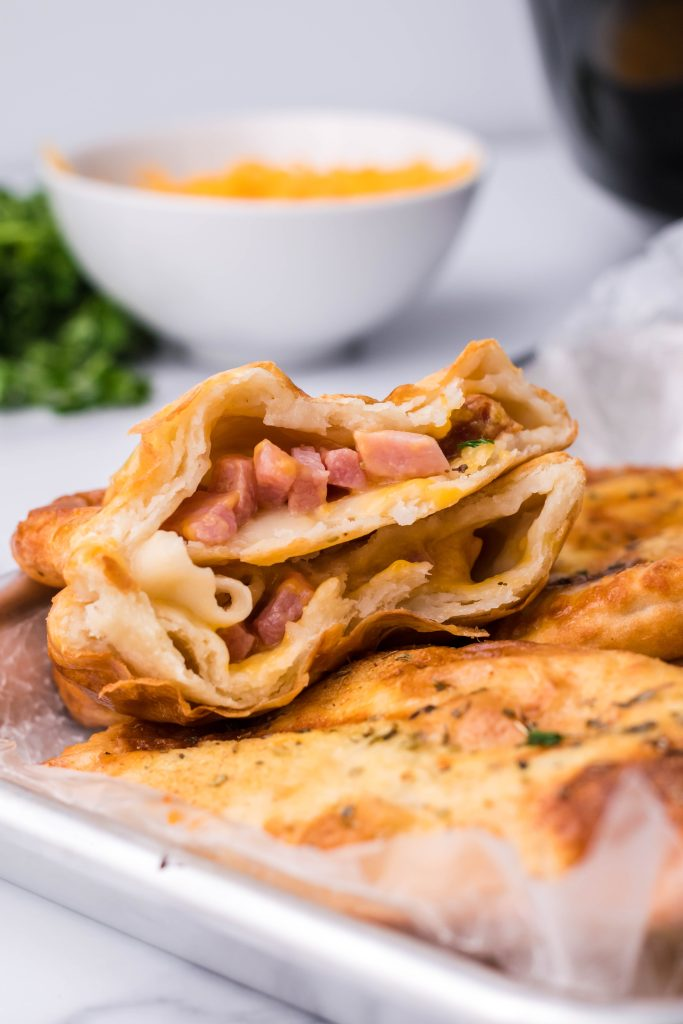 a ham and cheese filled air fryer hot pocket broken in half and shown on a white platter to reveal the ham and cheese filling