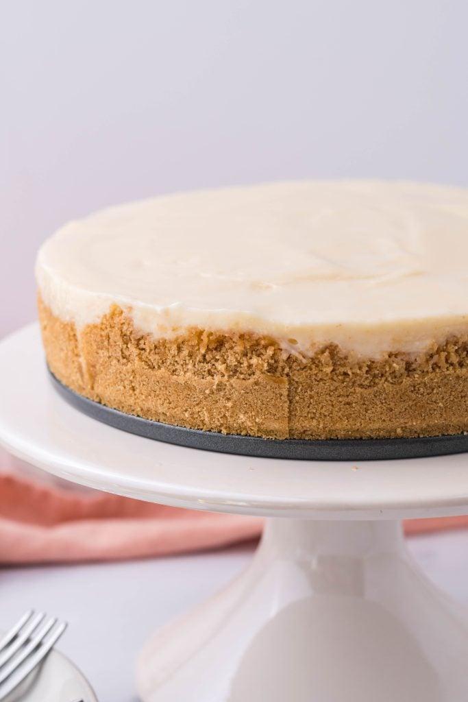 a cremora tart shown on a white pedestal cake stand