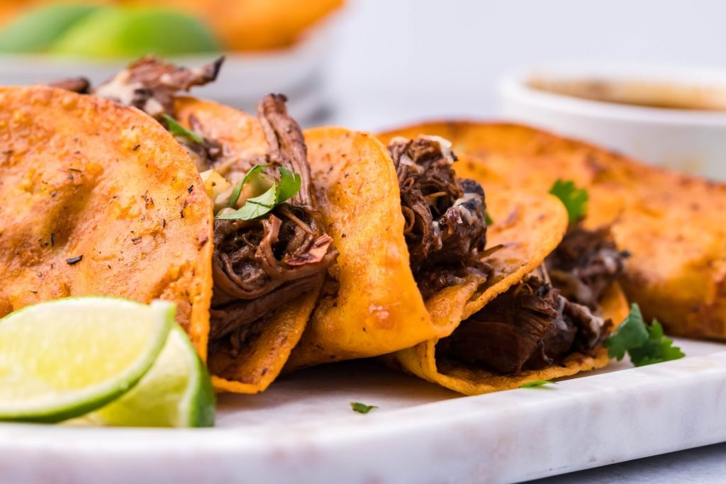 birria tacos shown on a white serving platter with lime wedges and a cup of the stewed juices for dipping