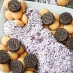 a purple Easter peeps themed cookies and cream cheese ball shown on a white plate surrounded with cookies for dipping