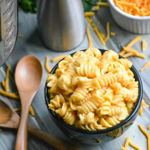 Instant Pot macaroni & cheese shown in a black bowl with wooden spoons on the side for serving
