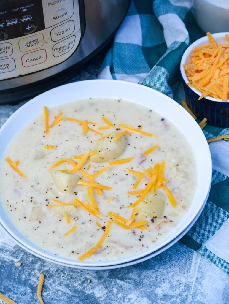 Classic Potato Soup In the Instant pot served in a white bowl with a pressure cooker and a bowl of shredded cheese in the background