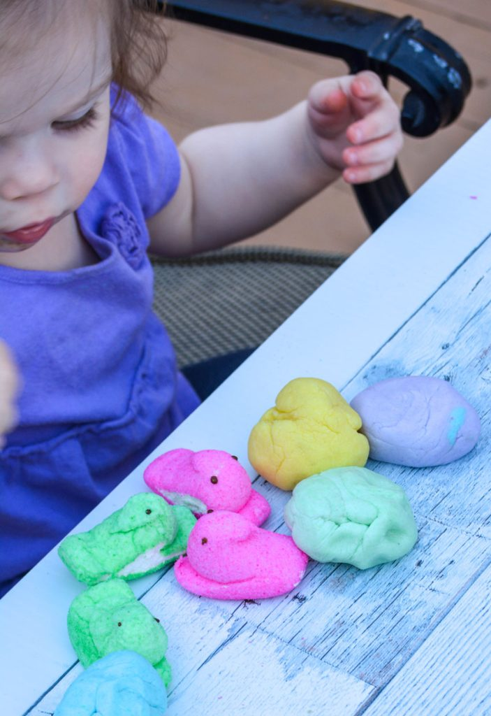 toddler shown playing with balls of edible peeps playdough and fluffy Easter marshmallows