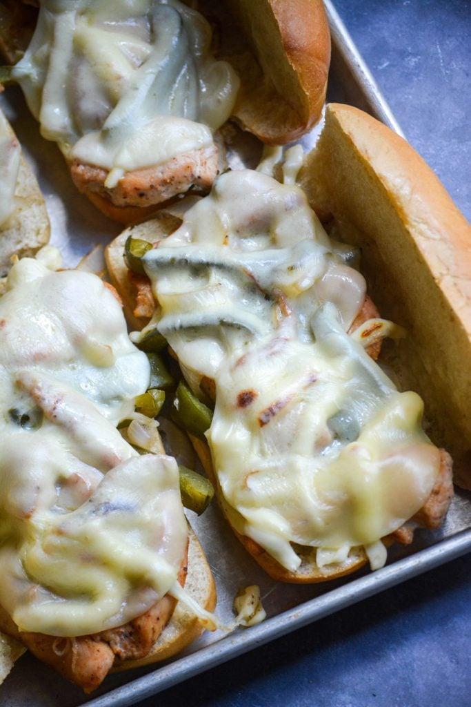 sheet pan philly chicken cheesesteaks assembled on fluffy hoagie rolls set on a sheet pan