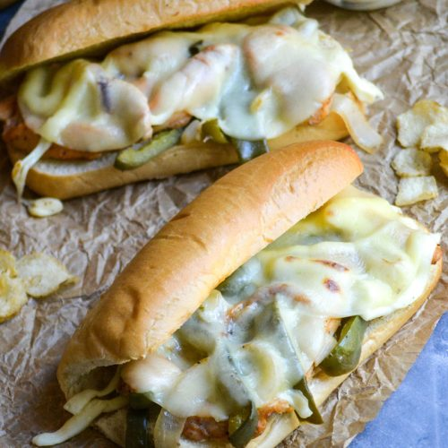 extra cheesy philly chicken cheesesteak sandwiches shown on wrinkled brown parchment paper