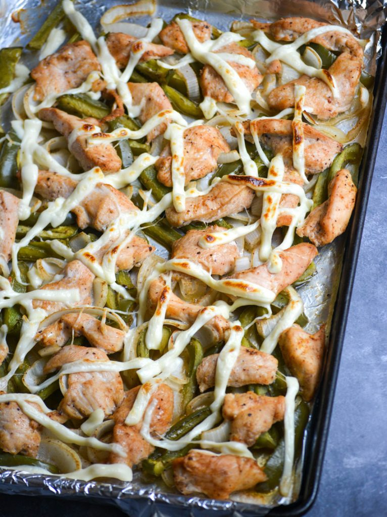sheet pan philly cheesesteak chicken and vegetables on a dark brown, seasoned sheet pan
