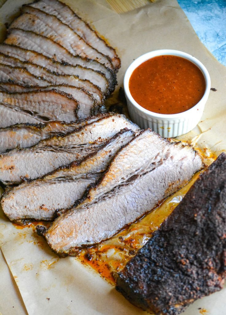 slices of juicy smoked brisket arrayed on a wooden cutting board