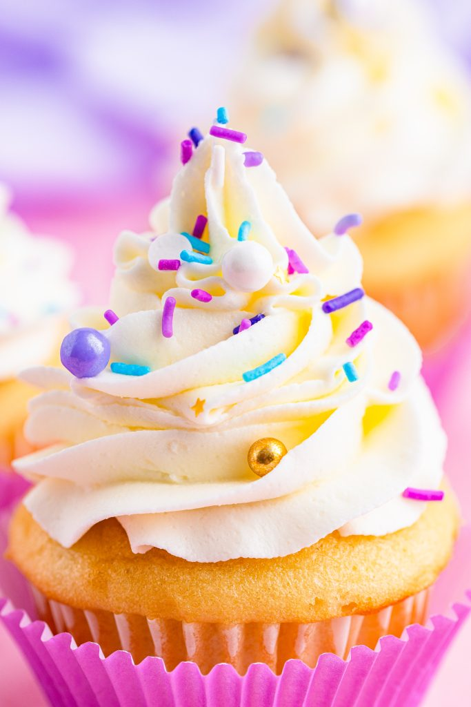 close up of a cupcake piled high with swirls of fluffy cake decorating frosting