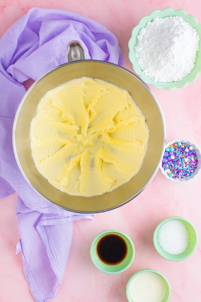 cake decorating frosting being shown mixed together in the bowl of a stand mixer