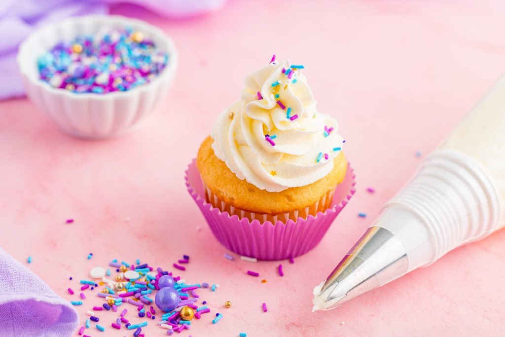 vanilla buttercream frosting shown in a fluffy mound on a yellow cupcake topped with colored sprinkles