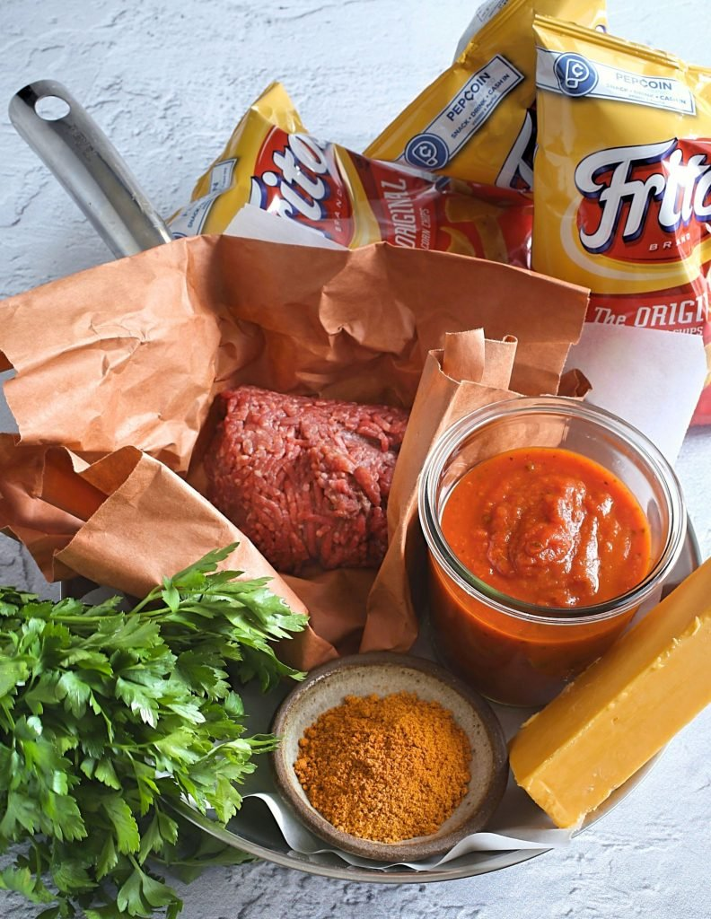 a photo showing all of the ingredients needed to make walking tacos with snack bags of fritos corn chips