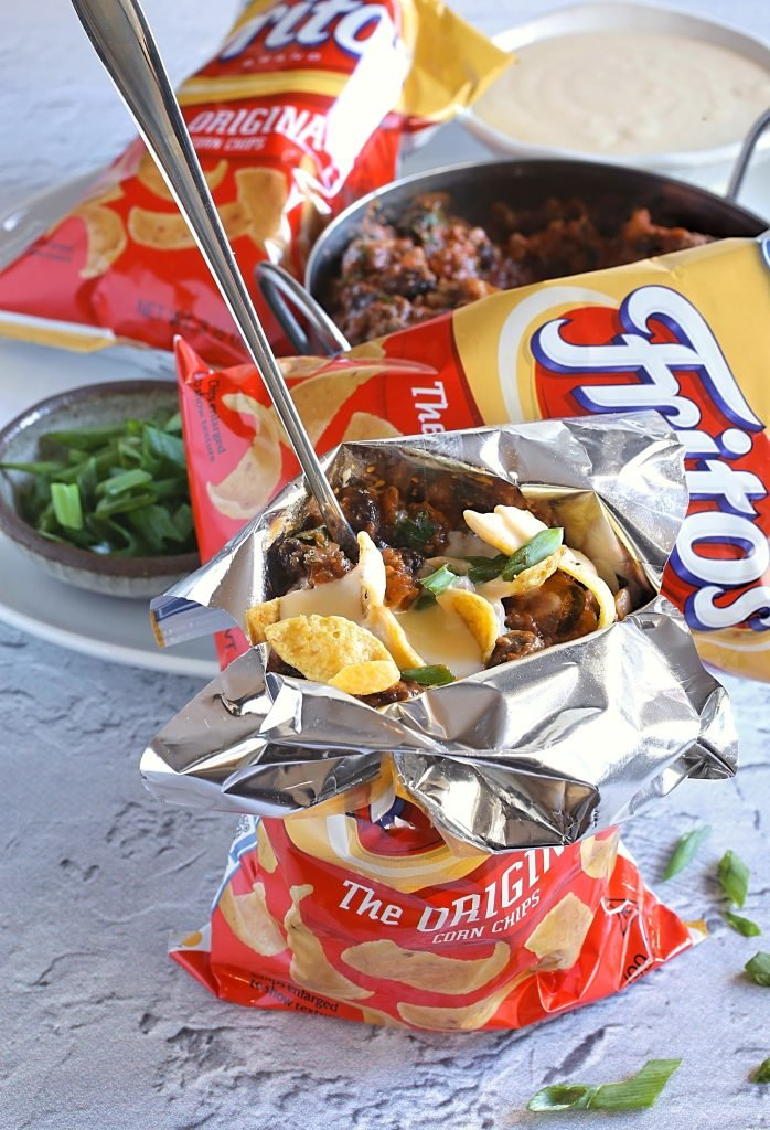 a walking taco bag shown split open with a long silver spoon sticking out