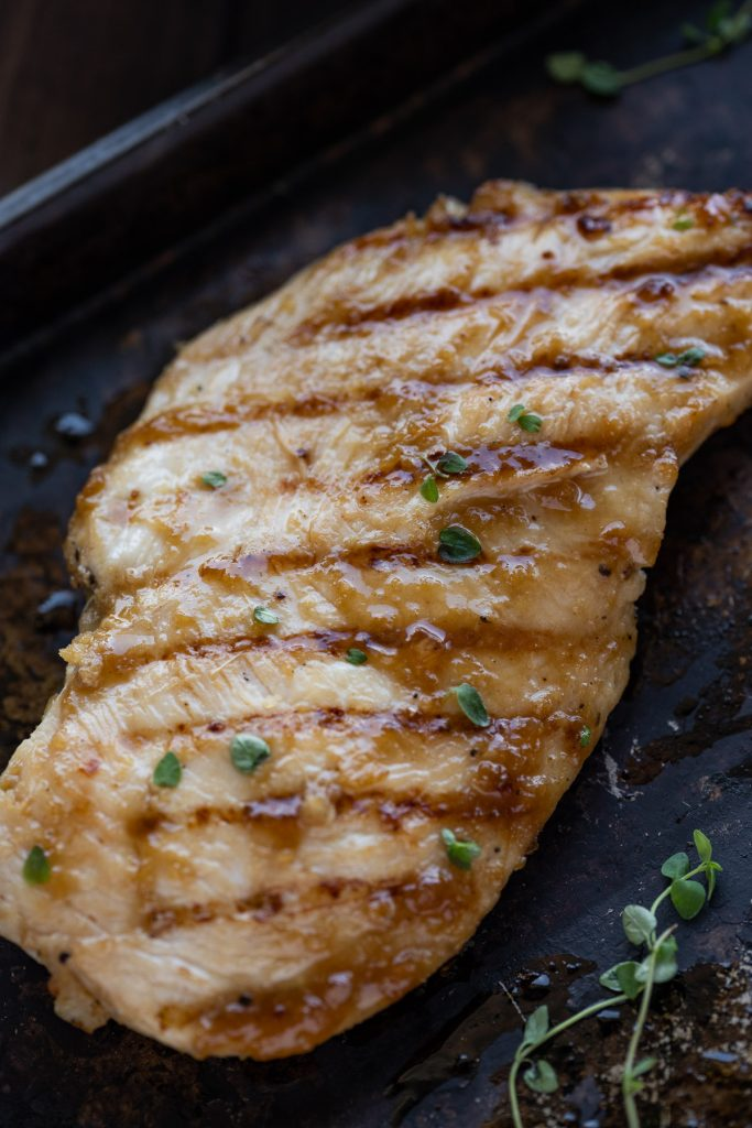 a single grilled teriyaki chicken breast shown on a black sheet pan with fresh herbs