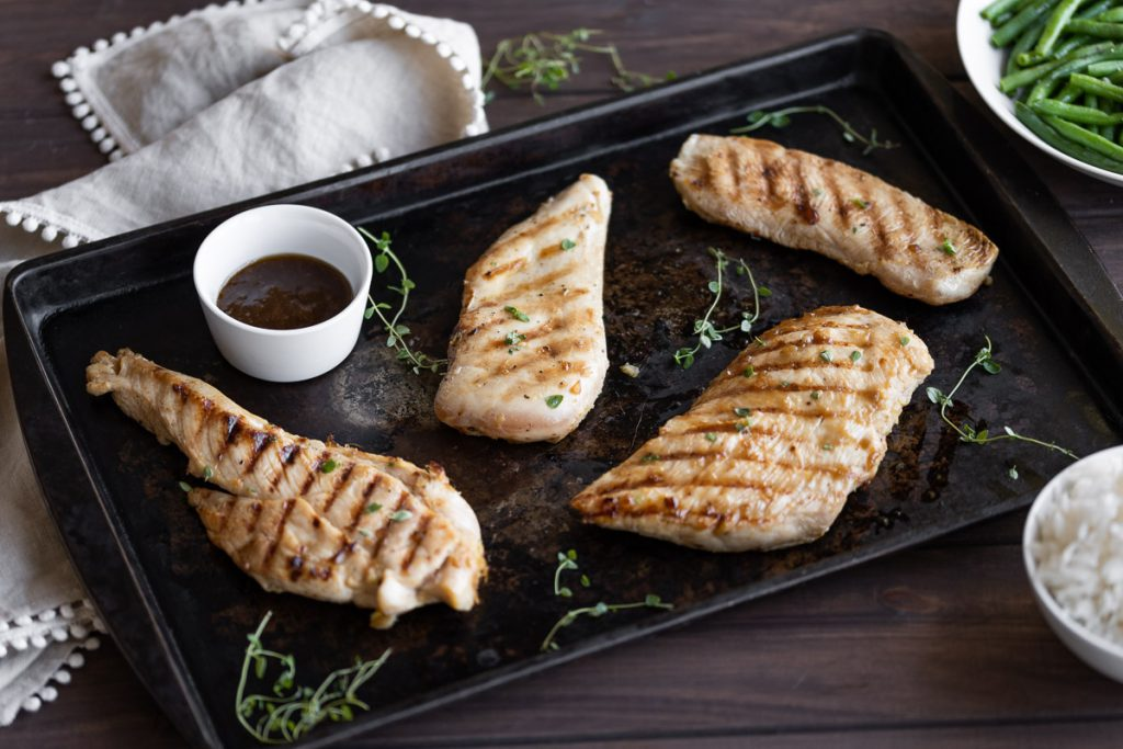 grilled teriyaki chicken on a black sheet pan with fresh herbs and sauce for dipping