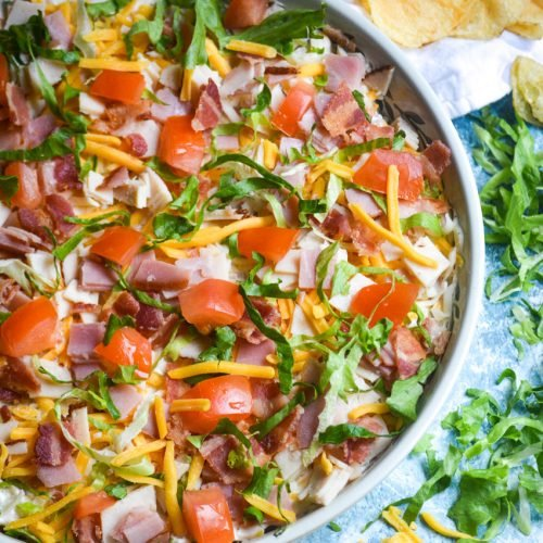 club sandwich dip shown in a large shallow bowl surrounded by chips and triangles of toasts for dipping