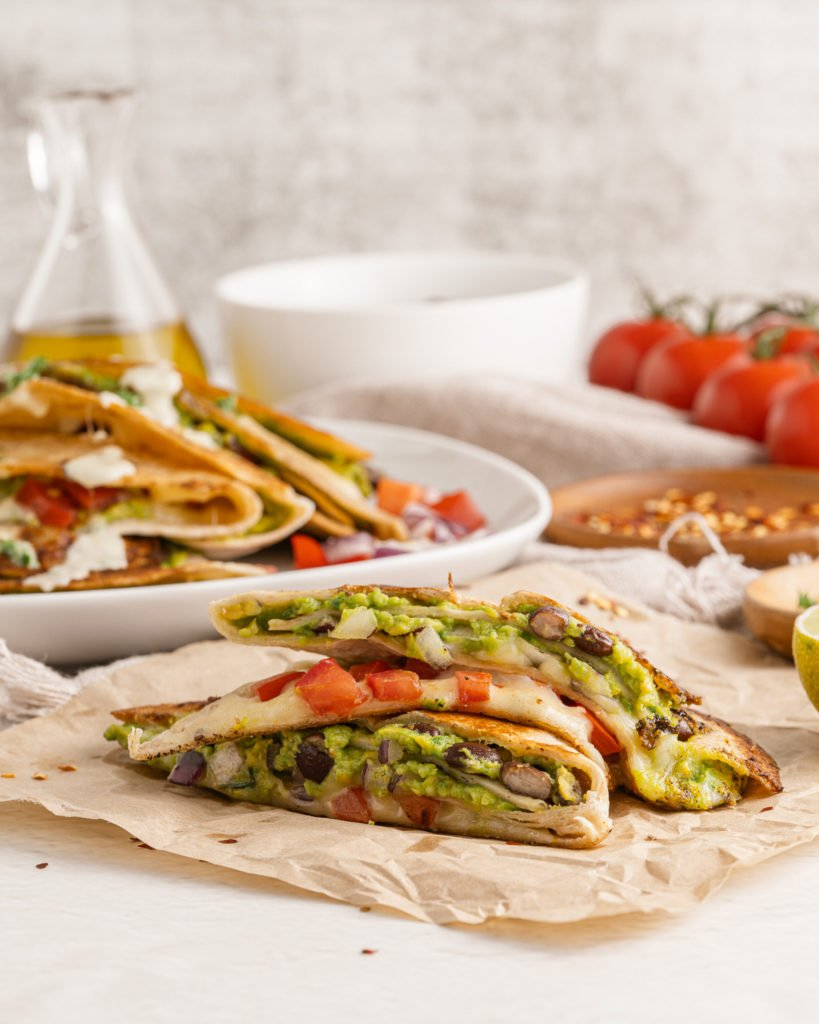 a guacamole bean and cheese stuffed quartered quesadillas cut in half to show the rich filling