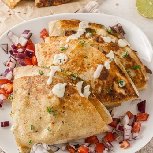 tiktok folded quesadillas stacked on a white plate, topped with tomatoes, red onions, cilantro, and drizzled with sour cream