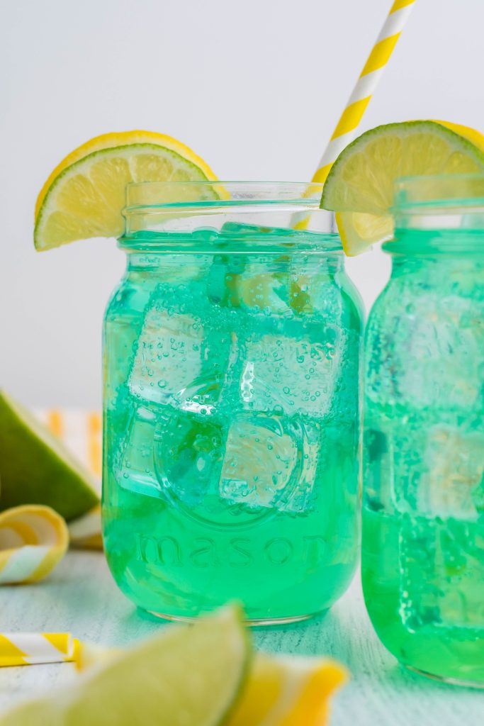 the best copycat baja blast recipe served over ice in clear glass jars with stripped yellow straw and sliced lemons for garnish
