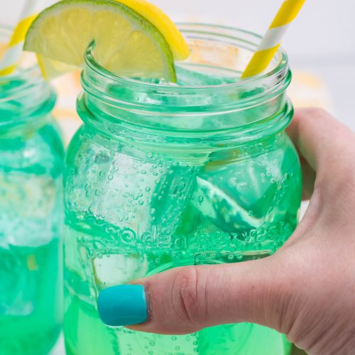a hand holding up a glass filled with copycat baja blast soda recipe over ice
