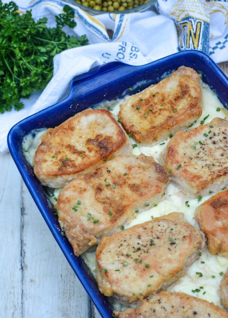 thick Farmer's style pork chops over a bed of creamy scalloped potatoes in a blue casserole dish