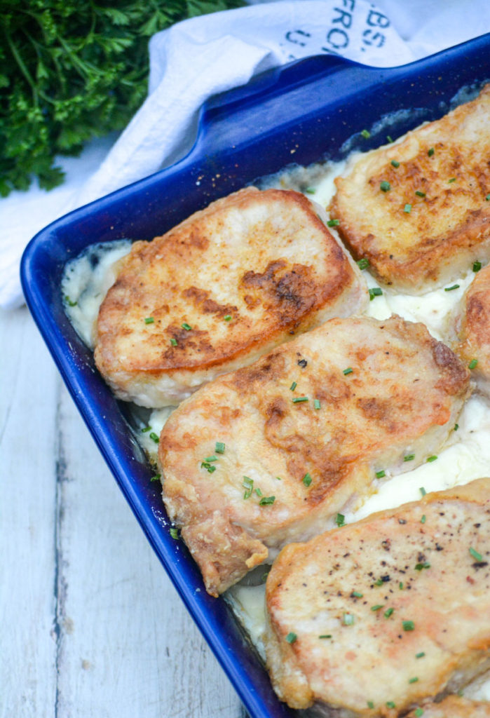 farmer's pork chops and potatoes served in a blue casserole dish