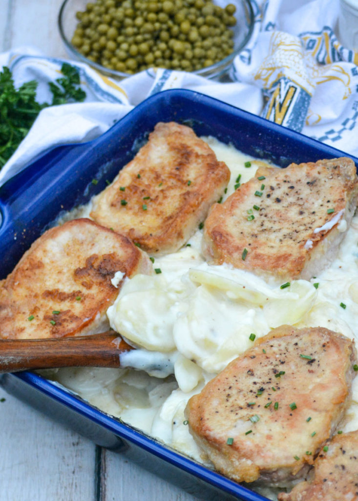 a wooden spoon shown scooping creamy scalloped potatoes from a blue casserole dish