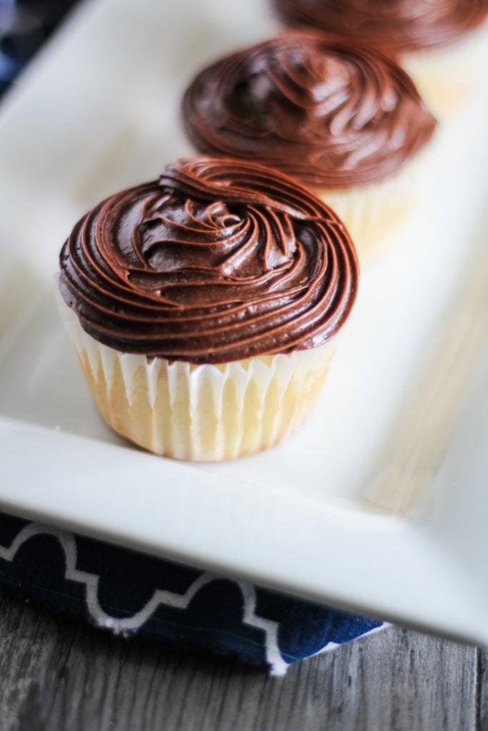 boston cream pie cupcakes on a white platter