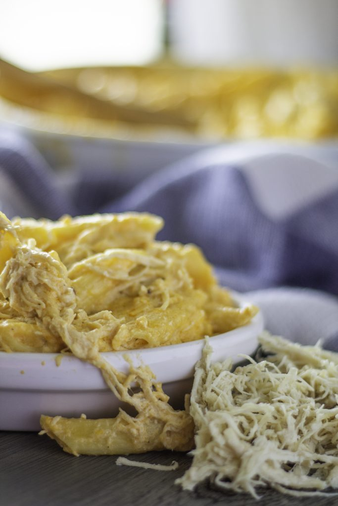 baked buffalo chicken mac and cheese shown in a white bowl with a fork stuck in it with a patterned cloth napkin and casserole dish in the background