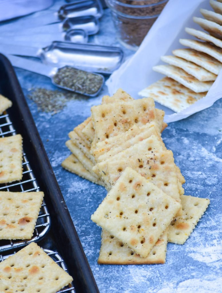a loose pile of savory Italian seasoned saltine crackers shown in the center or a blue counter with all of the ingredients staged evenly around them