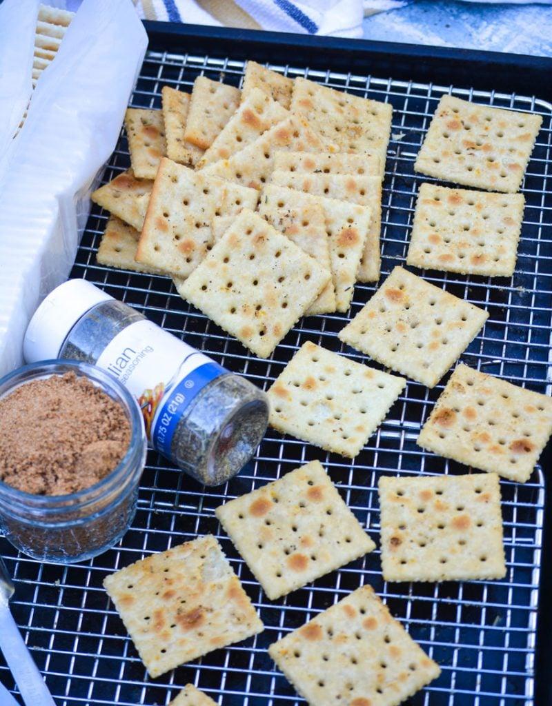 Italian seasoned saltine crackers shown on a wire baking rack with seasonings