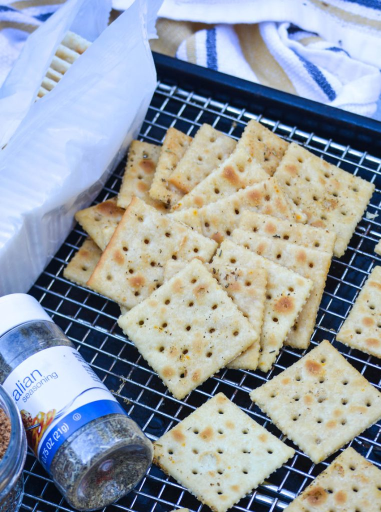 savory seasoned saltine crackers shown in a pile on a metal cooling rack set over a dark baking sheet