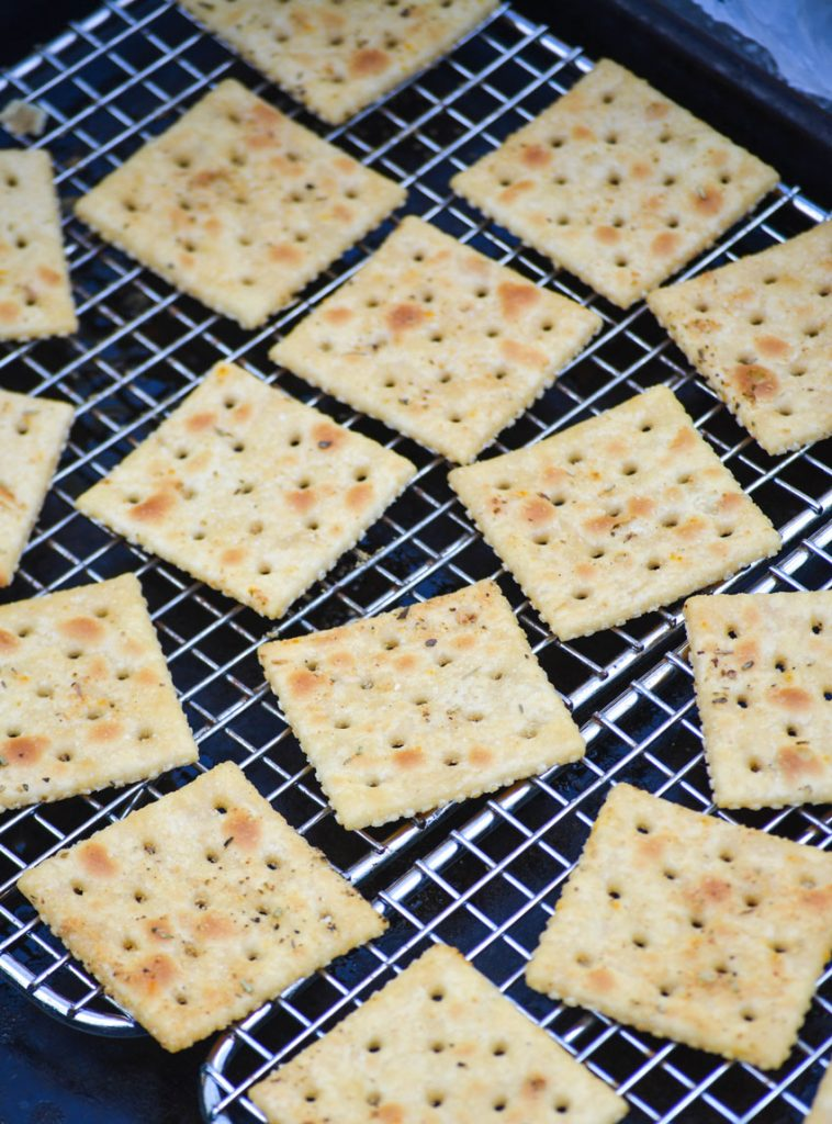 baked Italian seasoned saltine crackers sitting on a metal wire cooling wrap over top of a dark baking sheet