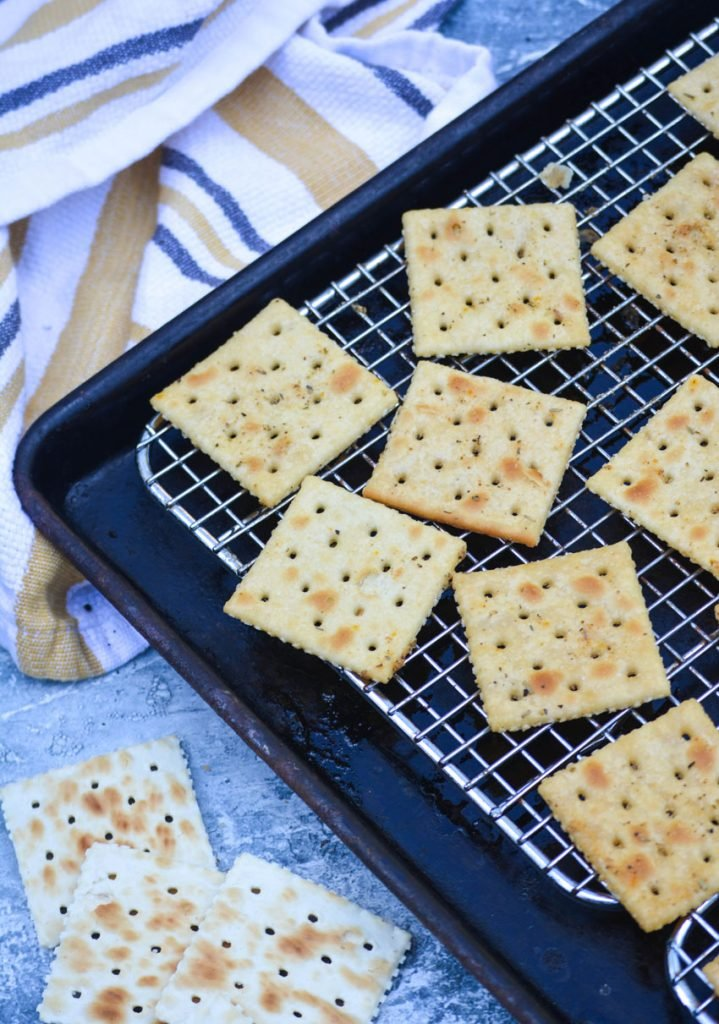 savory seasoned baked saltine crackers shown on a wire cooling rack set over top of a dark baking sheet