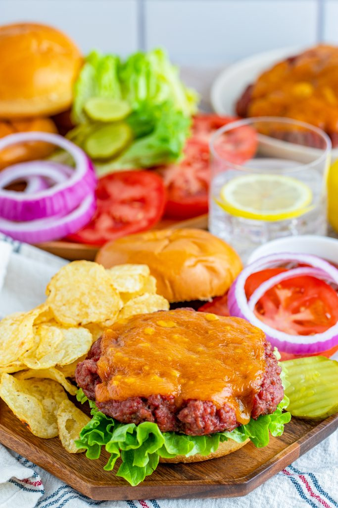 a smoked burger shown in a fluffy bun piled high with vibrant, fresh fixings and served on a wooden cutting board