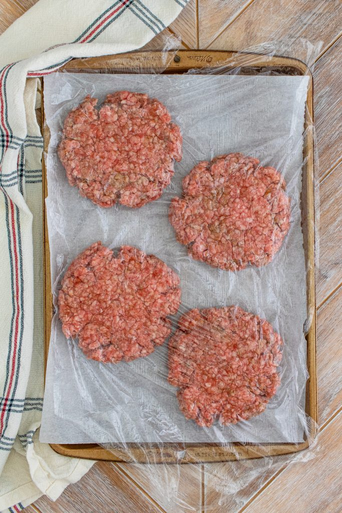 prepared burger patties shown on a sheet pan having just been flattened
