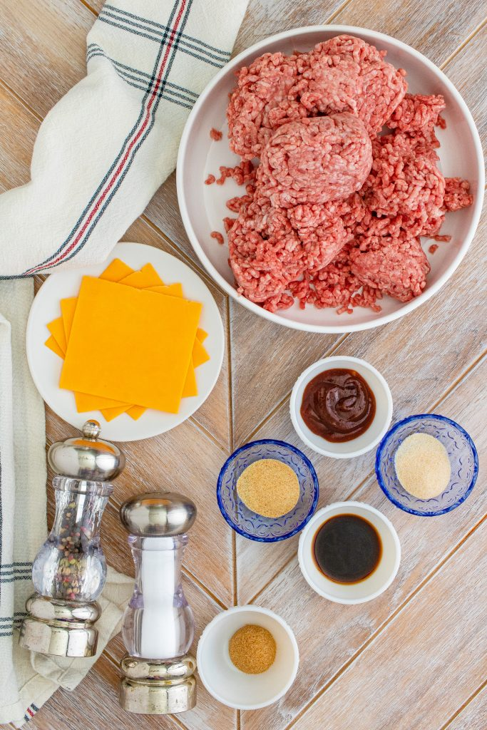 all the ingredients needed to make smoked burgers laid out on a wooden cutting board and pictured from above