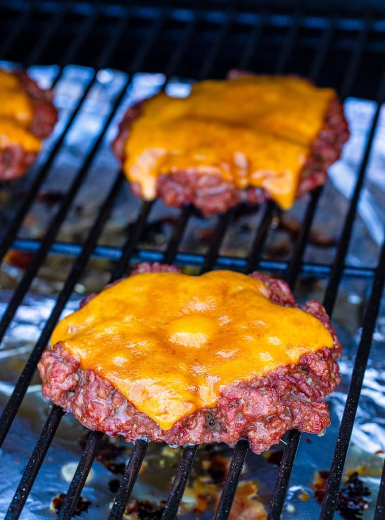 smoked burgers topped with melted cheese shown being smoked straight on the black grates of a grill