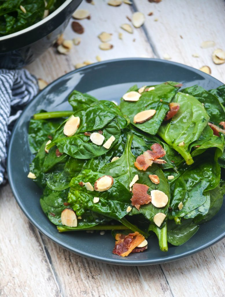 spinach salad served on a blue plate and topped with crumbled bacon and slivered almonds