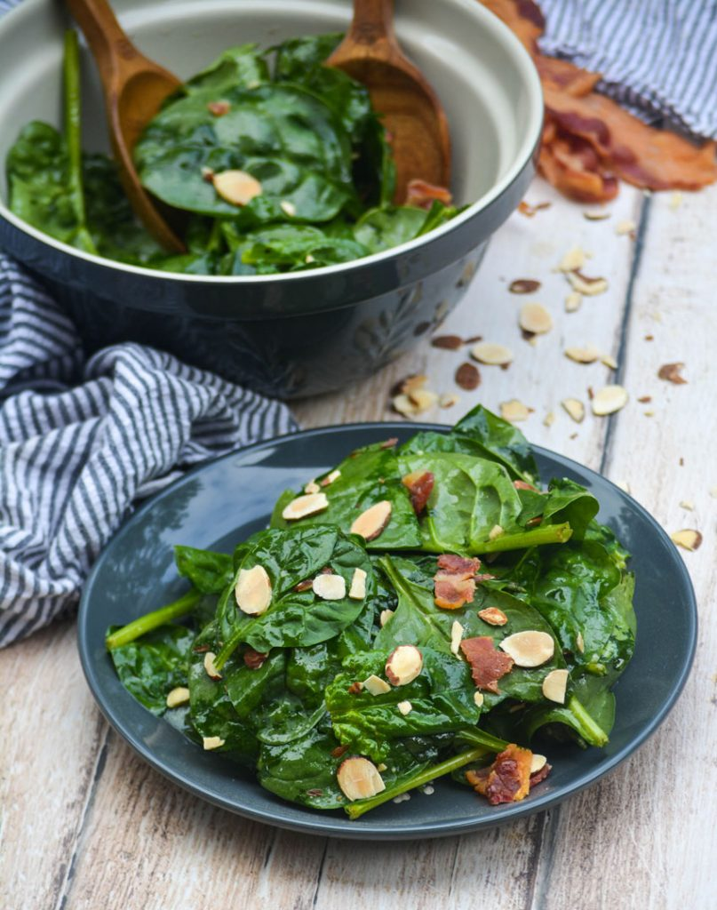 a plate of spinach salad shown with a blue mixing bowl and wooden utensils in the background