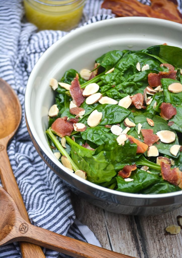 a blue ceramic mixing bowl filled with spinach salad topped with crisp bacon bits and sliced almonds
