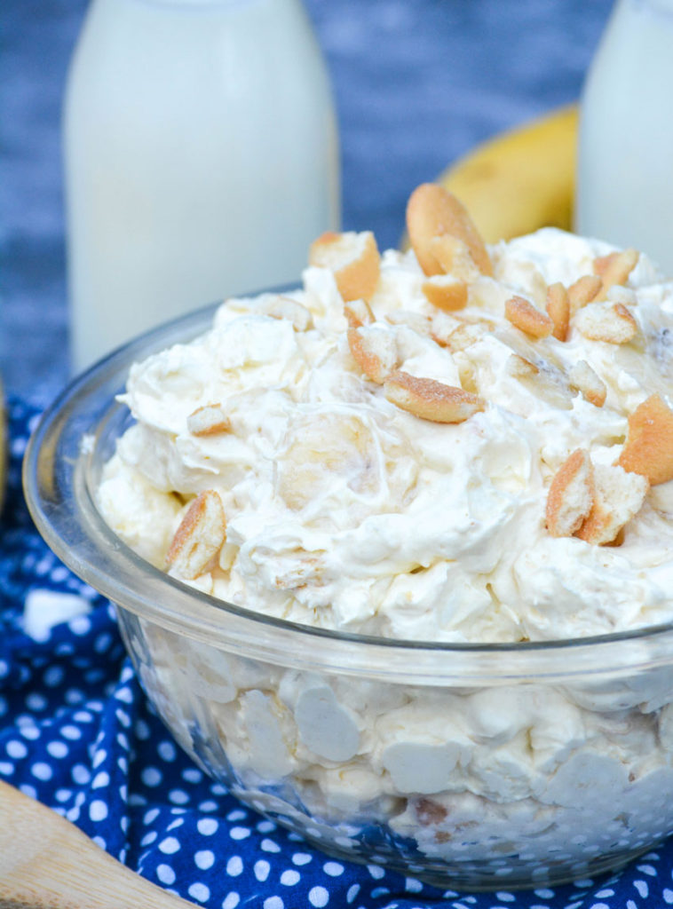 banana pudding fluff salad shown in a glass pyrex bowl topped with chopped vanilla wafers cookies