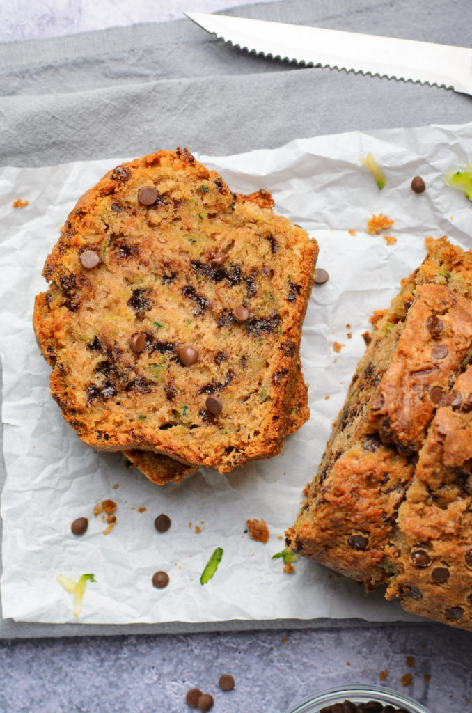 slices of chocolate chip zucchini bread stacked on a wrinkled sheet of white parchment paper