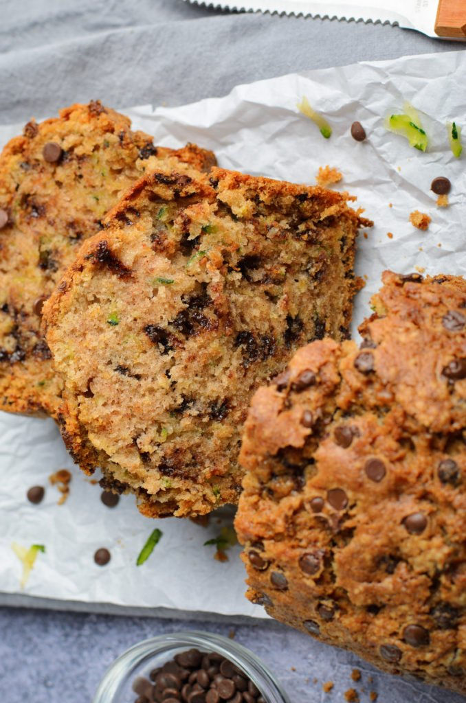 slices of chocolate chip zucchini bread shown on white parchment paper