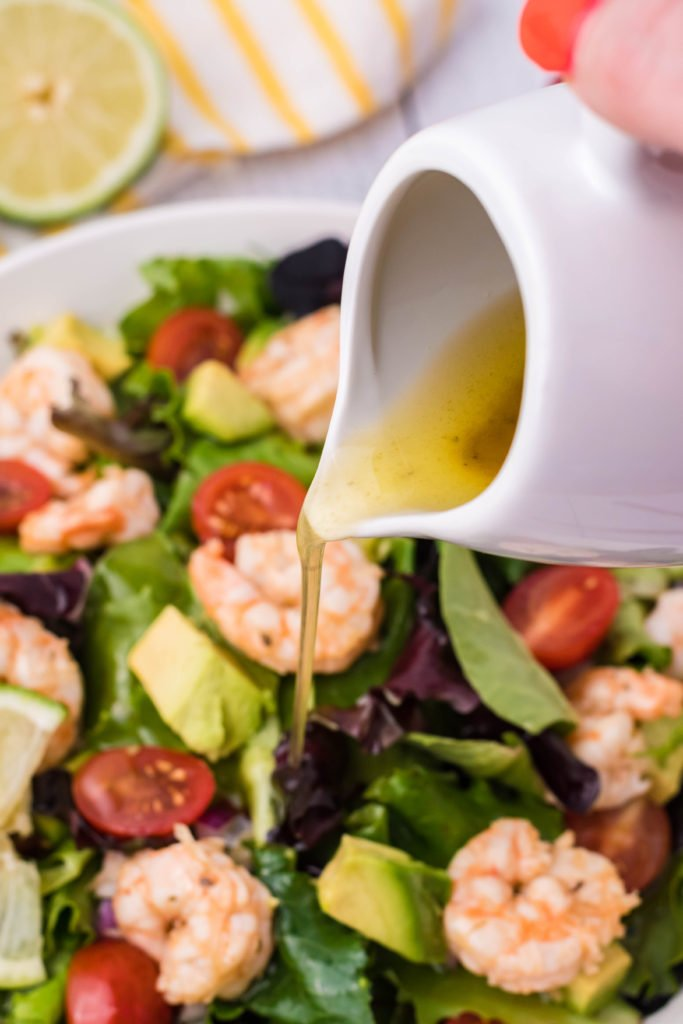 a small white pitcher shown pouring a zesty vinaigrette over a white bowl filled with fiesta lime shrimp salad