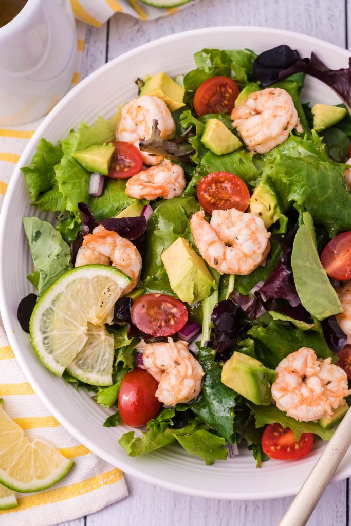 brightly colored fiesta lime shrimp salad shown in a white bowl garnished with fresh lime slices