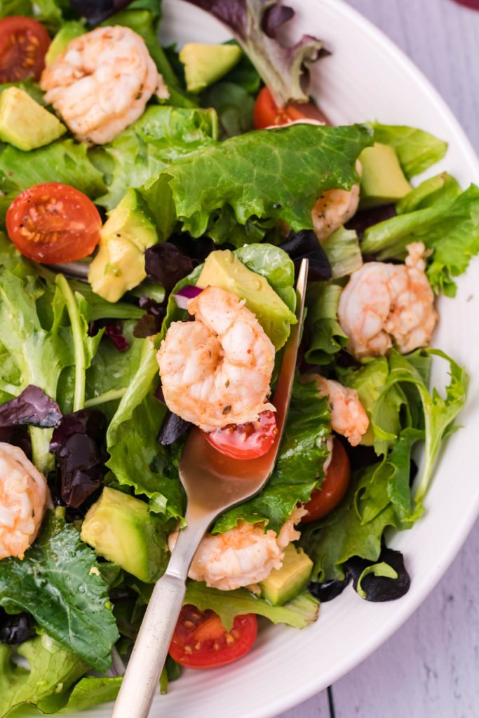 a silver fork shown with fiesta lime shrimp held over a bowl of salad greens