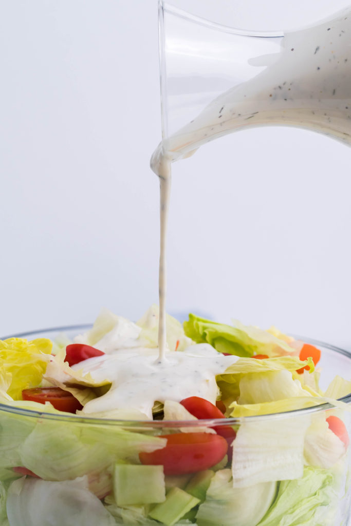 homemade ranch dressing being poured from a glass jar onto a waiting salad