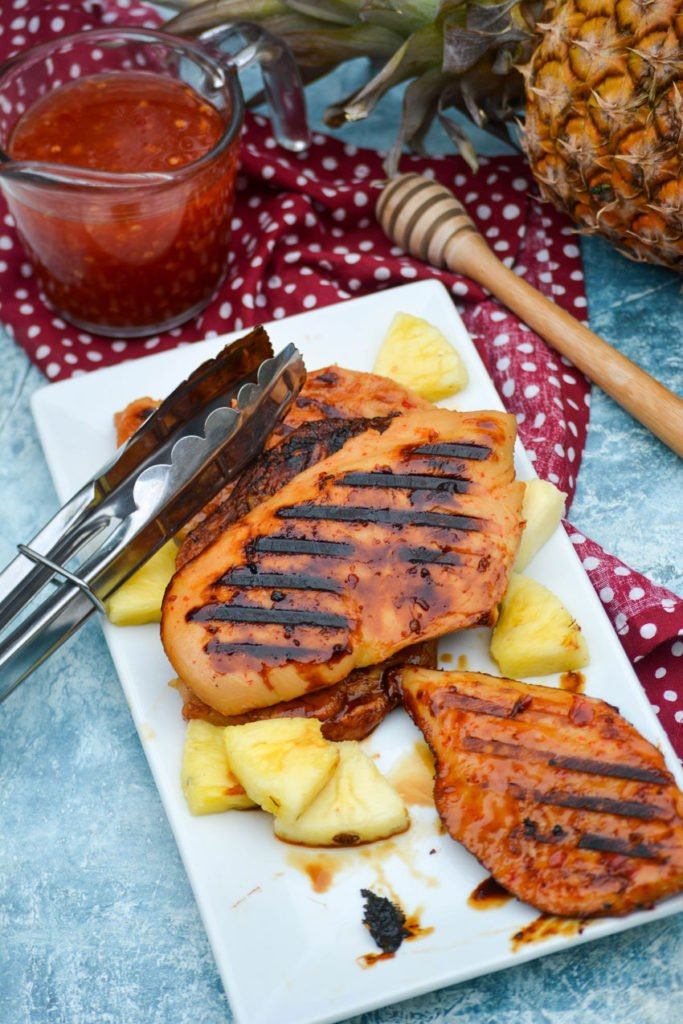 grilled pineapple chicken shown on a white platter with a pair of silver tongs