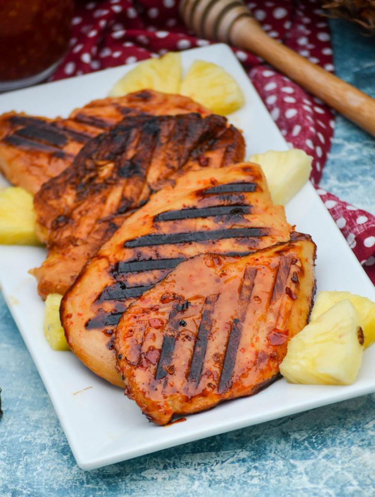 grilled pineapple chicken shown on a white platter with chunks of fresh pineapple and a pair of silver tongs