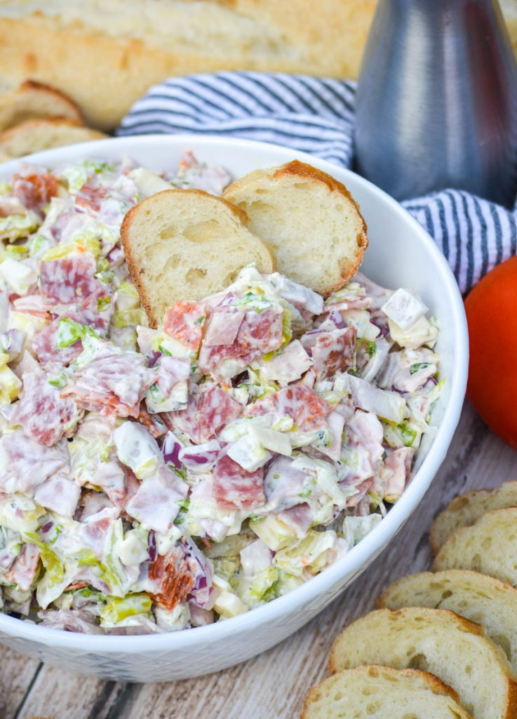 Italian hoagie dip shown in a white bowl with two baguette slices sticking out of the top of the dip